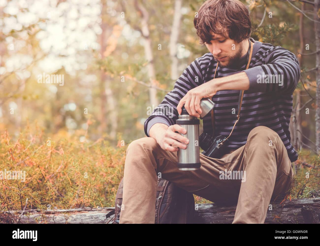 Hombre viajero relax en bosque con termos, mochila y cámara de fotos de Viajes Vacaciones en concepto de estilo Imagen De Stock