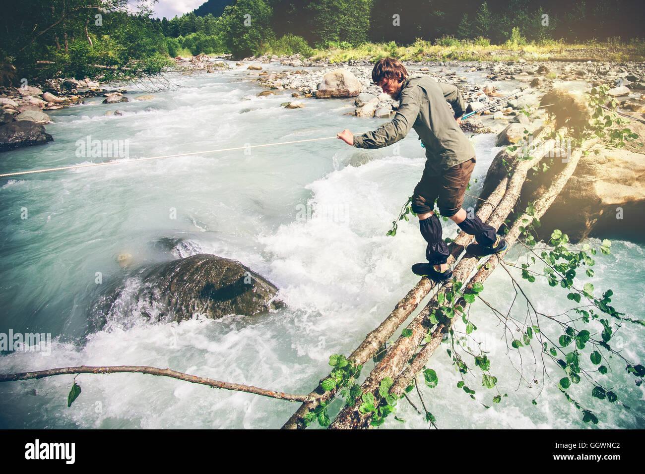 Hombre viajero cruzar río en maderas de estilo de vida al aire libre Concepto de supervivencia extremas de Imagen De Stock