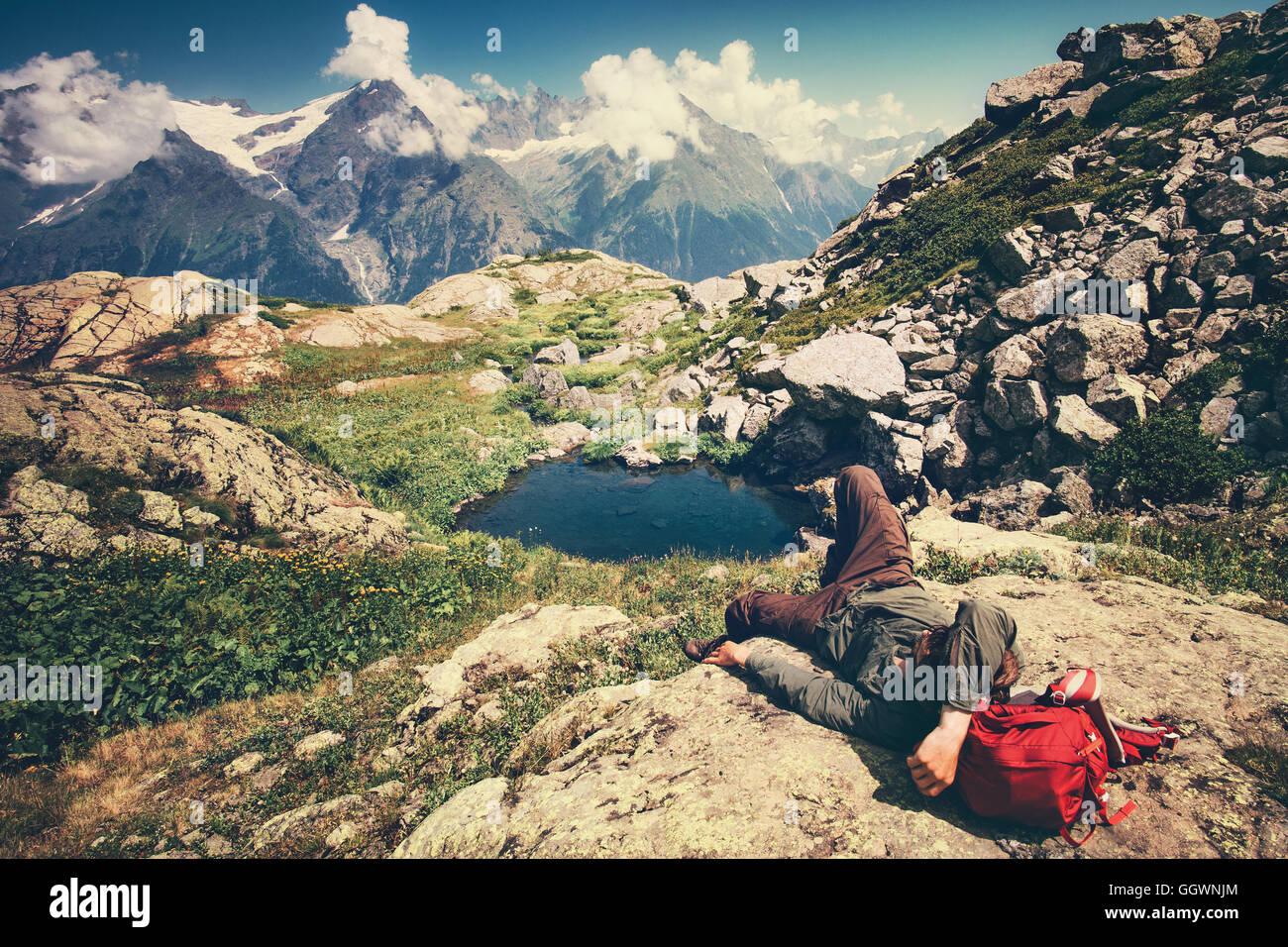 Hombre viajero sentando relajante viaje con mochila concepto de estilo de vida sereno paisaje de las montañas Imagen De Stock