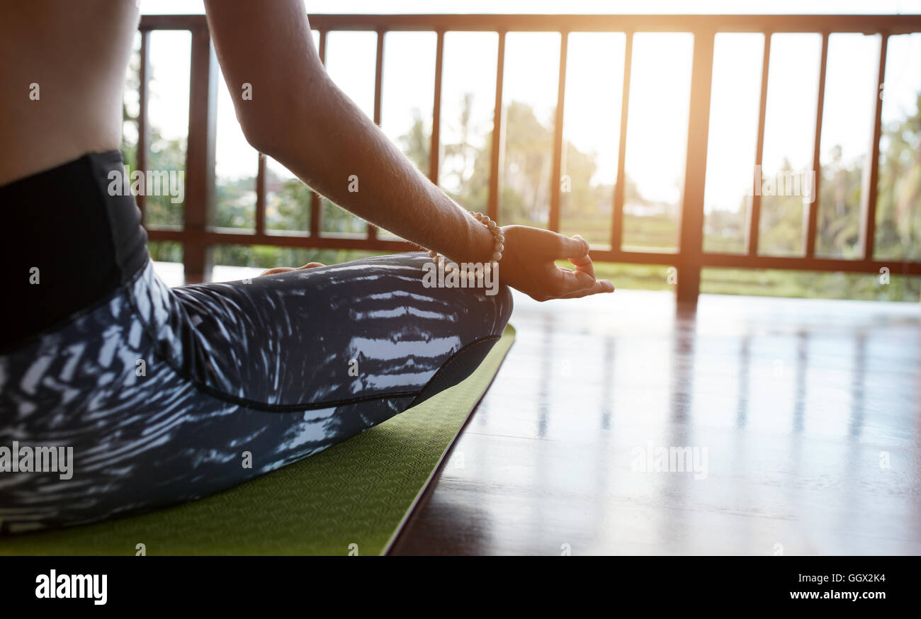 Cerca de la mujer sentada sobre la colchoneta de ejercicios con las piernas cruzadas y las manos sobre las rodillas. Imagen De Stock