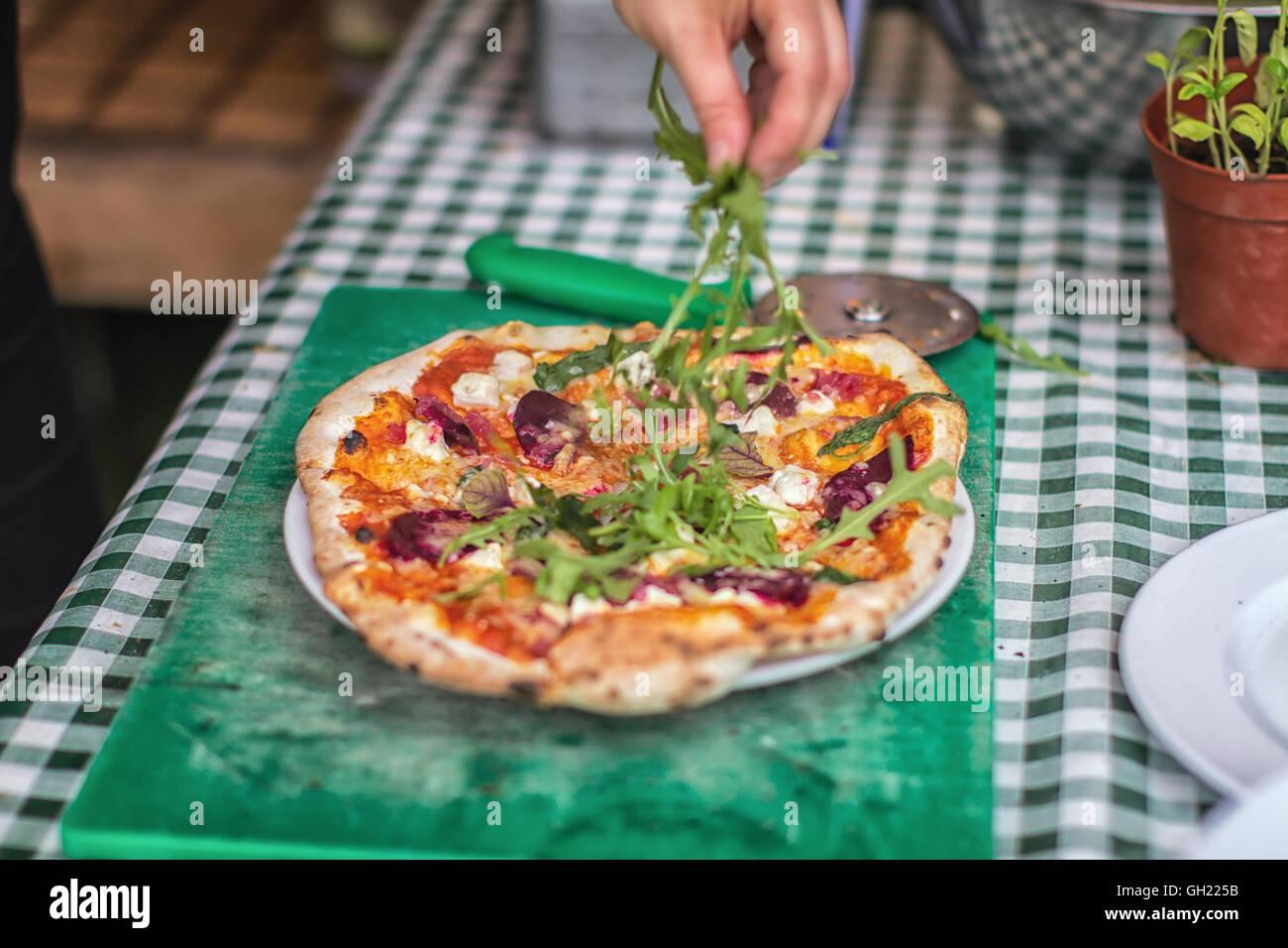 Corteza delgada italiana pizza vegetariana con hojas de rúcula ser rociados sobre ella Imagen De Stock