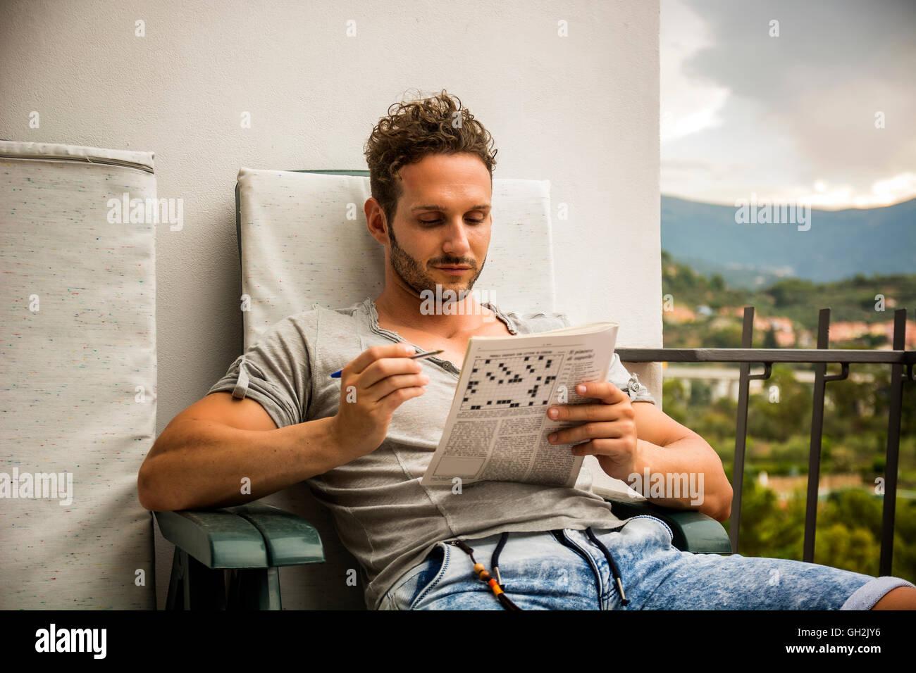 e6489145040ec Hombre joven sentado haciendo un crucigrama mirando cuidadosamente en una  revista