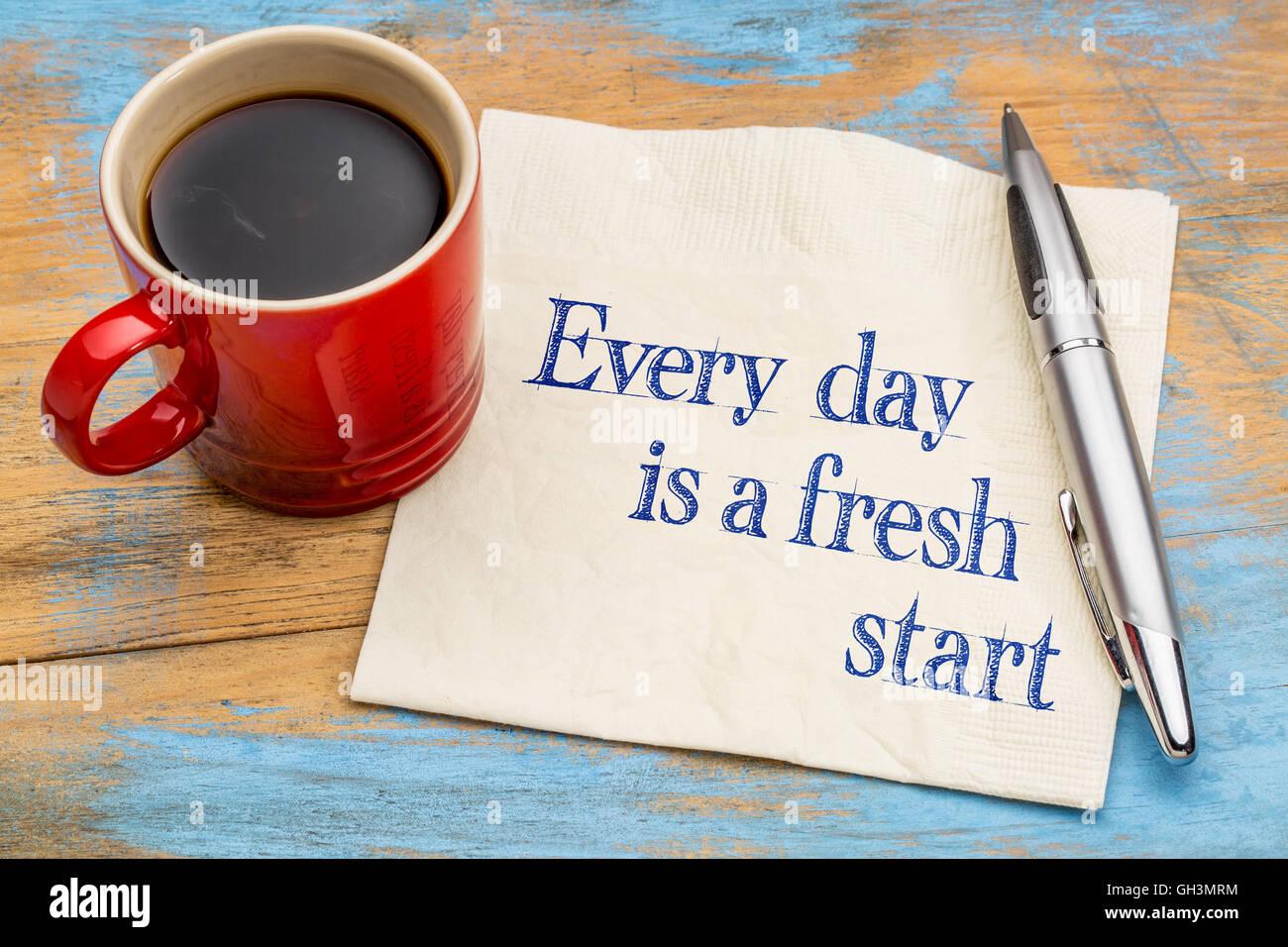 Cada día es un nuevo comienzo - escritura motivacional en una servilleta con una taza de café. Imagen De Stock
