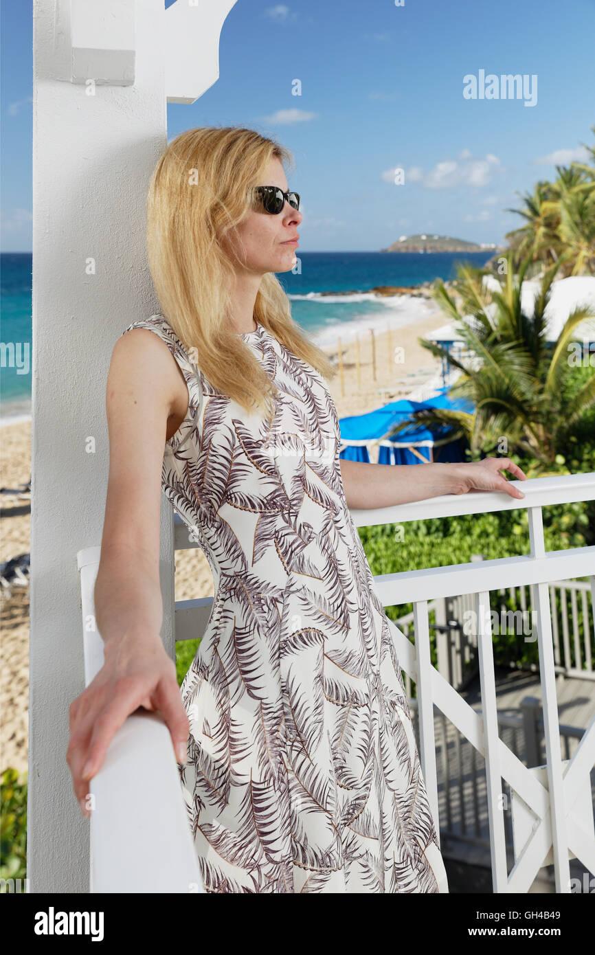 Vista vertical de una mujer rubia en un vestido de verano de pie en un balcón de un resort de playa y relax, Imagen De Stock