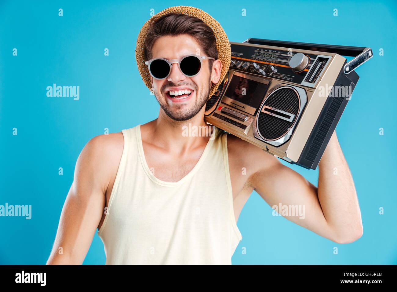 Retrato de feliz joven con gorra y gafas de sol con un radiocasete Imagen De  Stock a5120ef55cf4