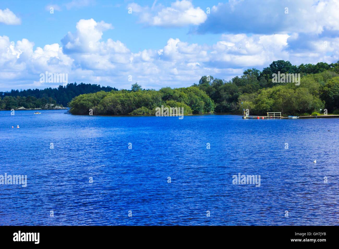 La gente remando en canoa a remo en calma azul lago Loch Lomond en Escocia Foto de stock