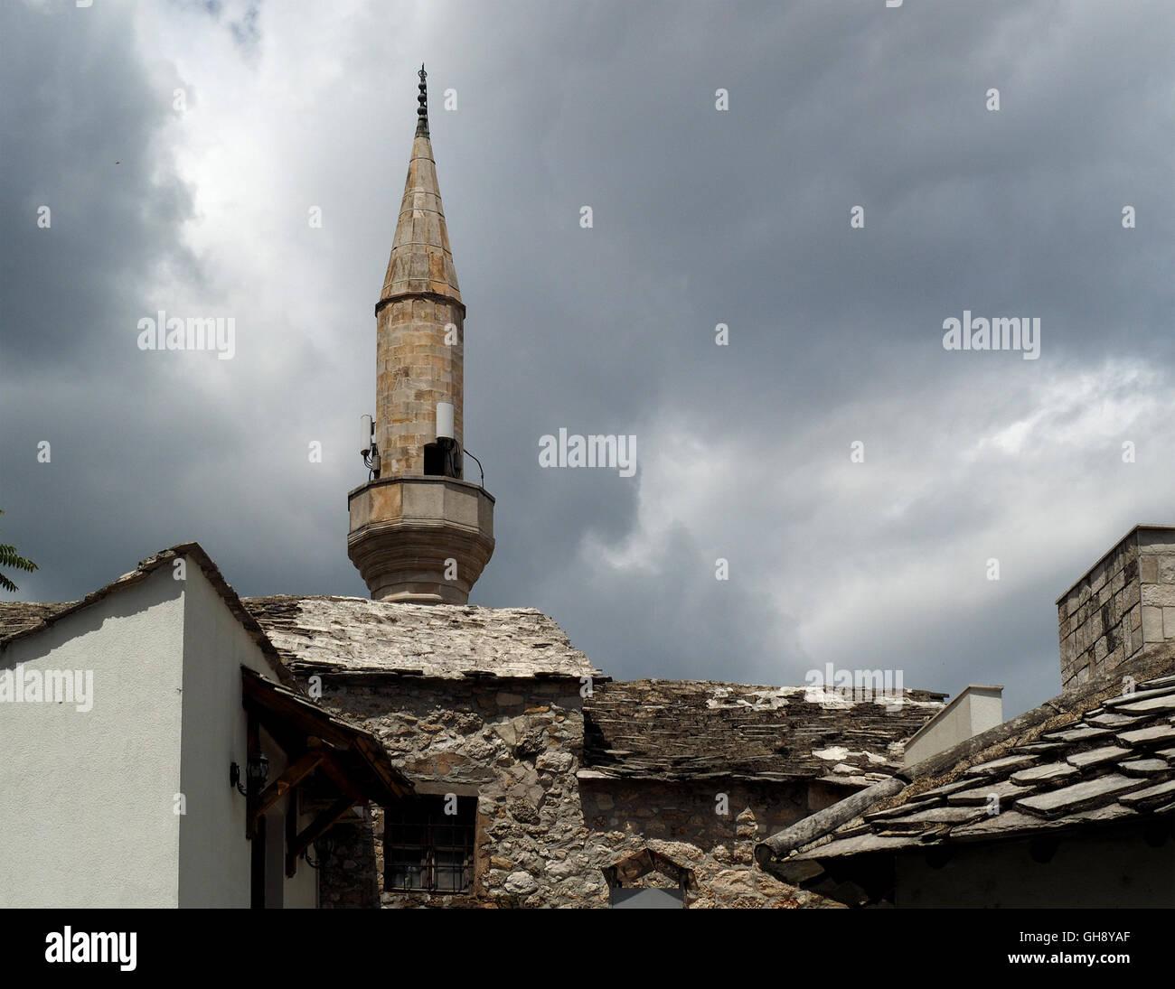 Torre de la mezquita con altavoces para la llamada a la oración y de la piedra y las tejas de típica arquitectura vernácula de Mostar en Bosnia y Herzegovina Foto de stock