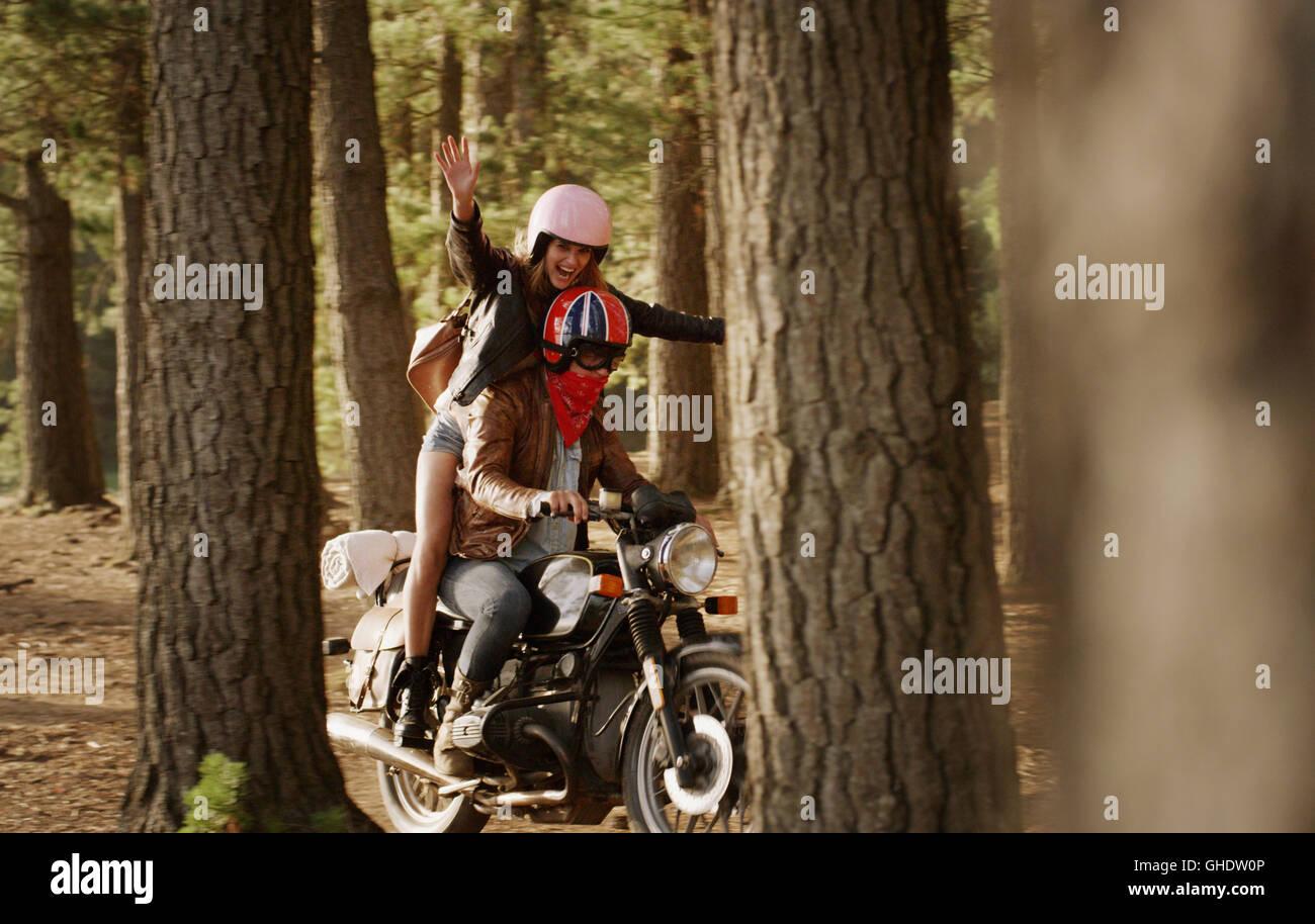 Exuberante mujer joven montando en motocicleta woods Imagen De Stock