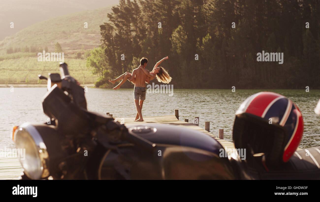 Hombre joven llevando una exuberante mujer en lakeside dock detrás de motocicleta Foto de stock