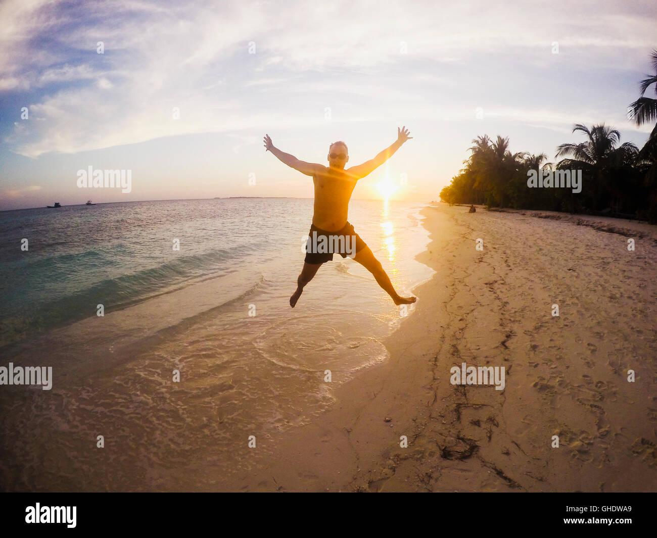 Retrato del hombre exuberante saltando sobre playa tropical al atardecer Foto de stock