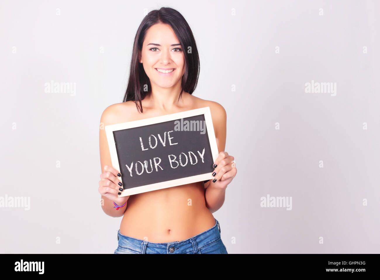 Mujer joven la celebración de pizarra que lee el amor a tu cuerpo. El amor propio concepto. Imagen De Stock