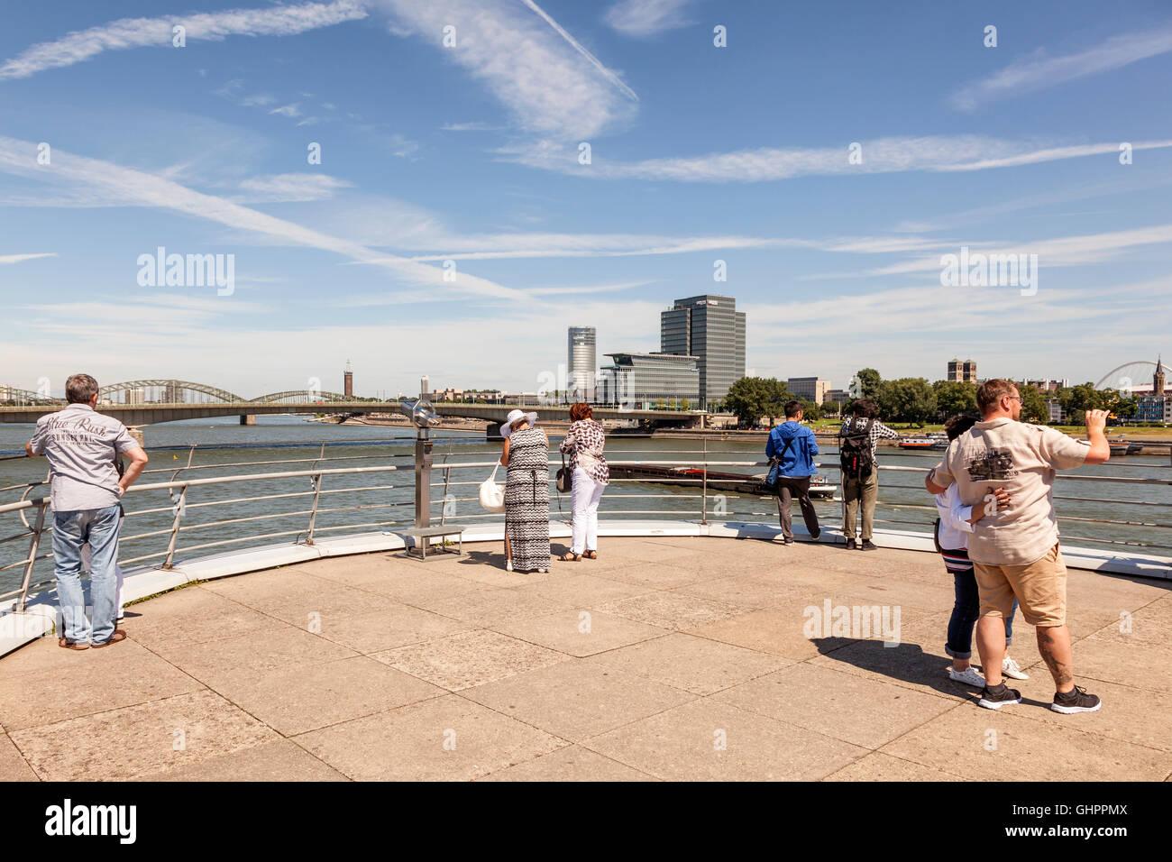 Los turistas en el paseo del río Rin, con una bonita vista de la ciudad de Colonia, Alemania Imagen De Stock