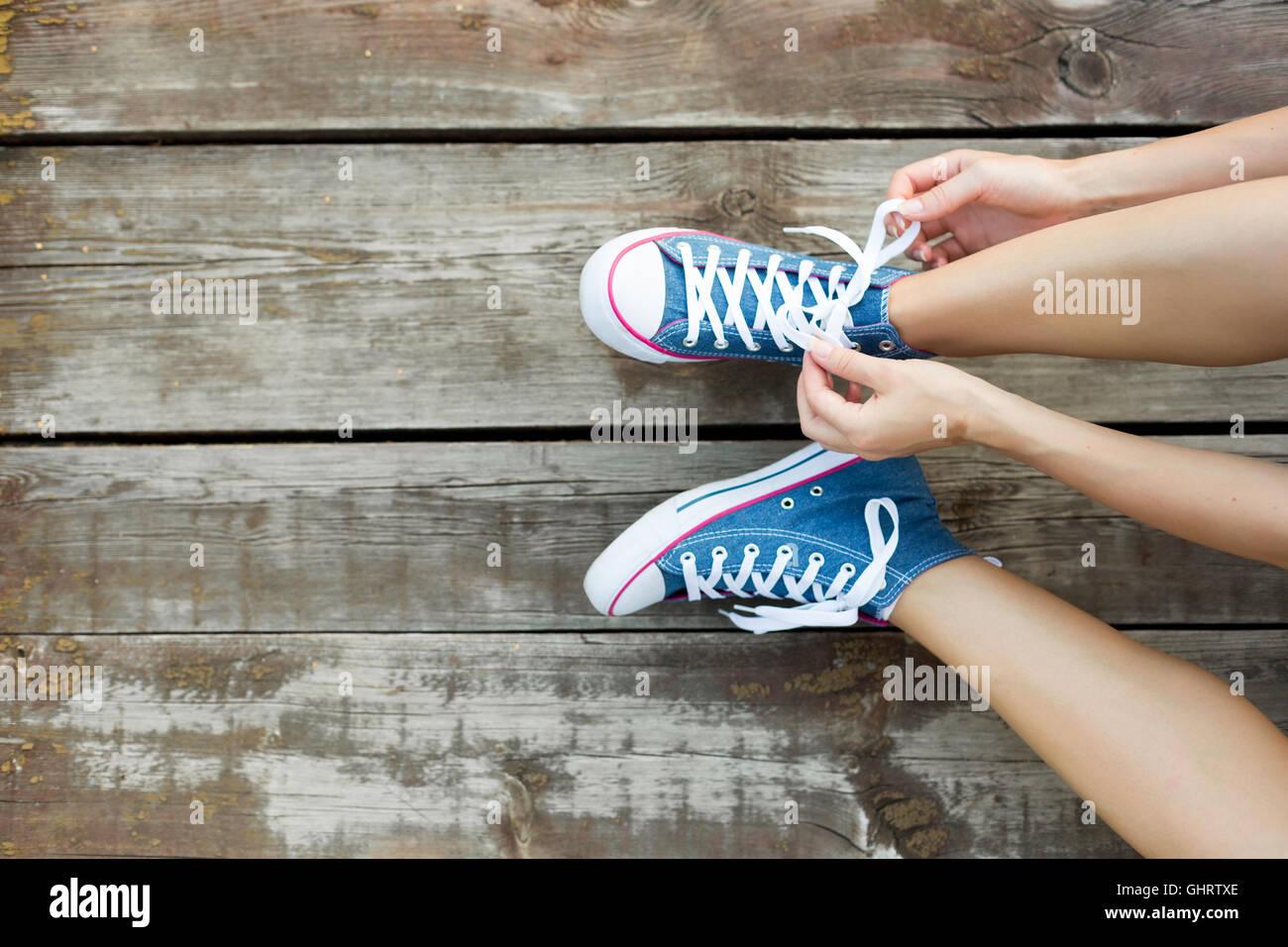 Mujer joven atar los cordones de sus zapatillas de vaqueros sentados en el piso de madera Imagen De Stock