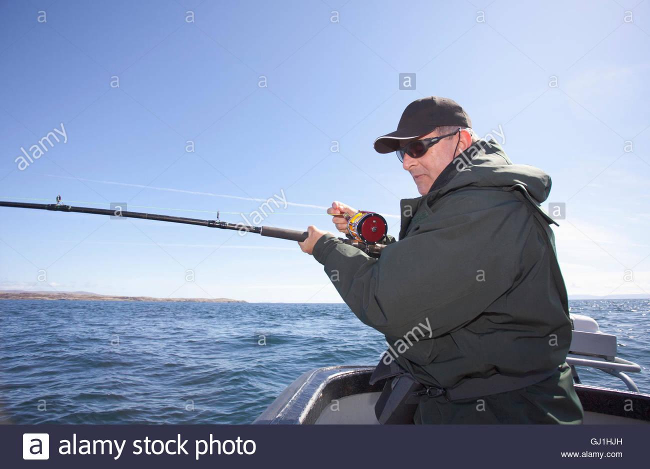 Un hombre de pesca y vida silvestre durante un viaje en barco de pesca frente a la costa de la isla de Harris, Hébridas Imagen De Stock