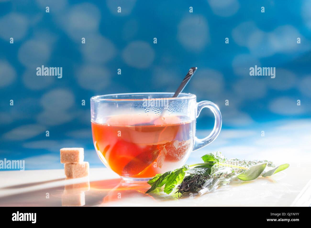 Taza de Té con azúcar y hierbas en día soleado. Imagen De Stock
