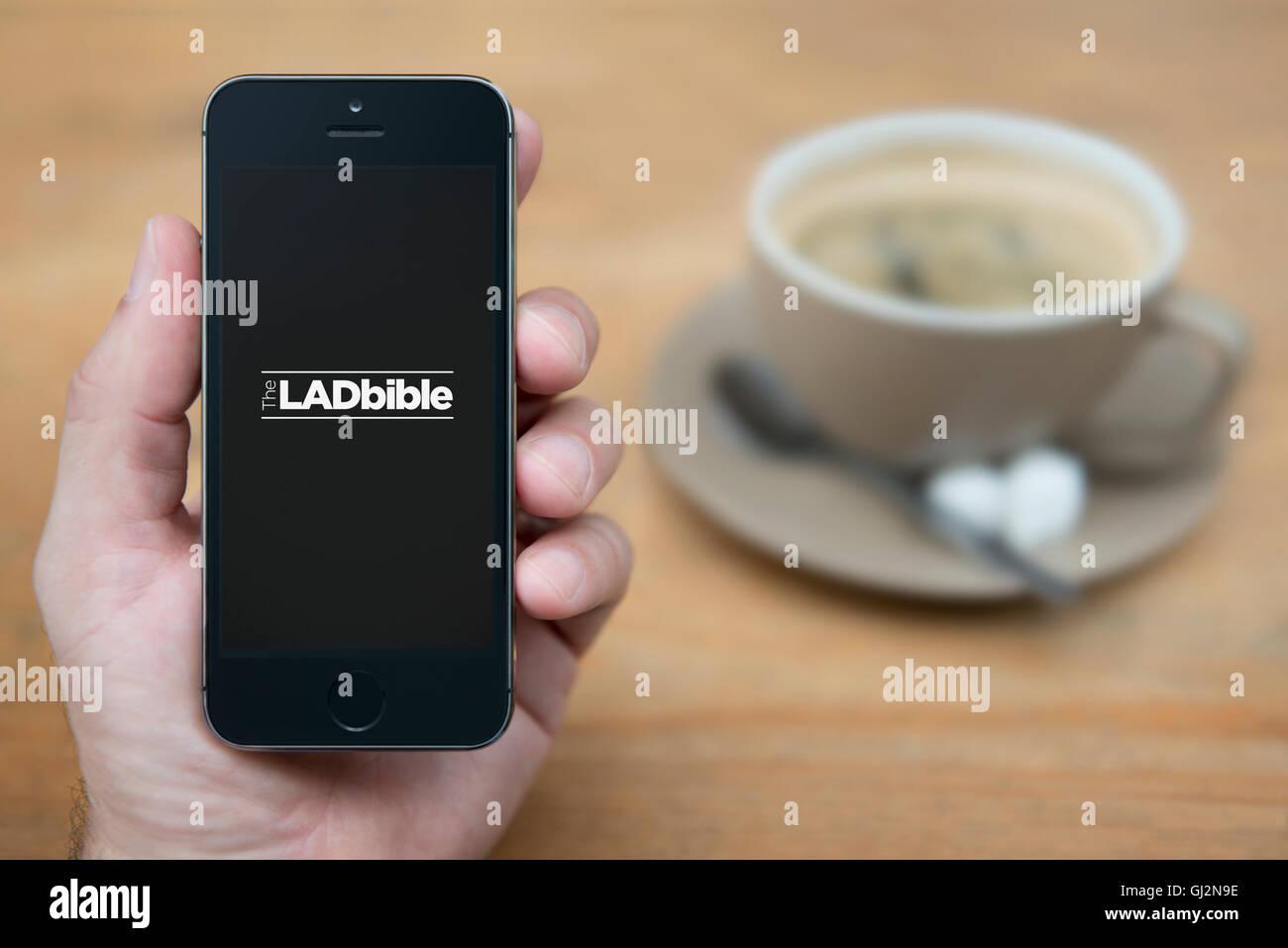 Un hombre mira el iPhone que muestra el logotipo de Biblia Lad, mientras se sentó con una taza de café Imagen De Stock