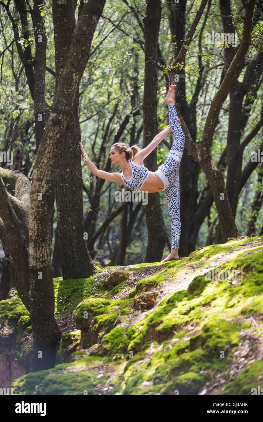 Mujer en roca de pie sobre una sola pierna estiramiento Imagen De Stock