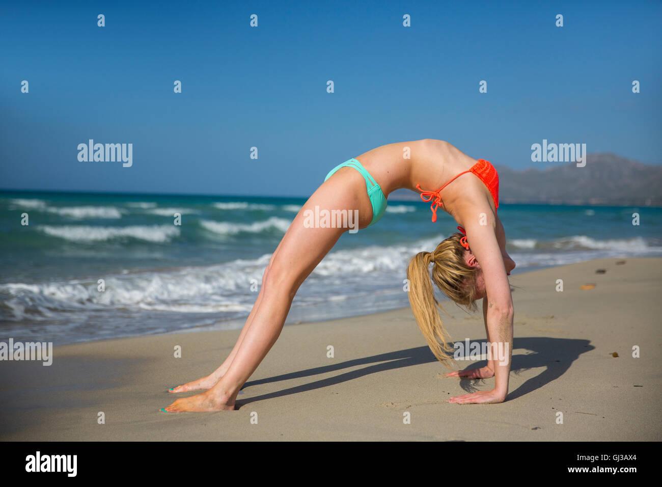 Mujer joven en la playa, hacer ejercicio, doblada hacia atrás Imagen De Stock