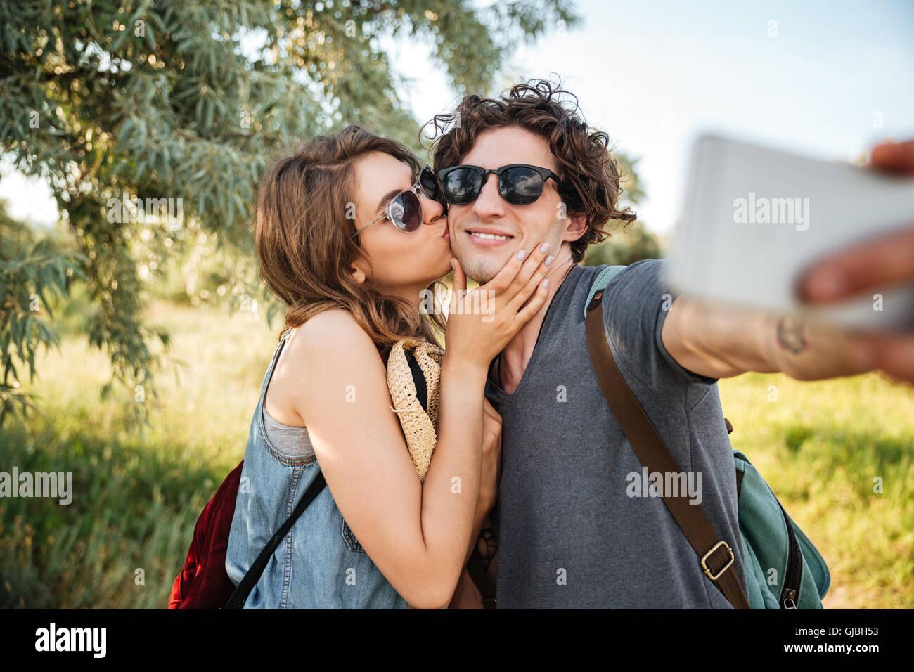 Sonriente joven pareja feliz con mochilas senderismo en el bosque y haciendo selfie Imagen De Stock