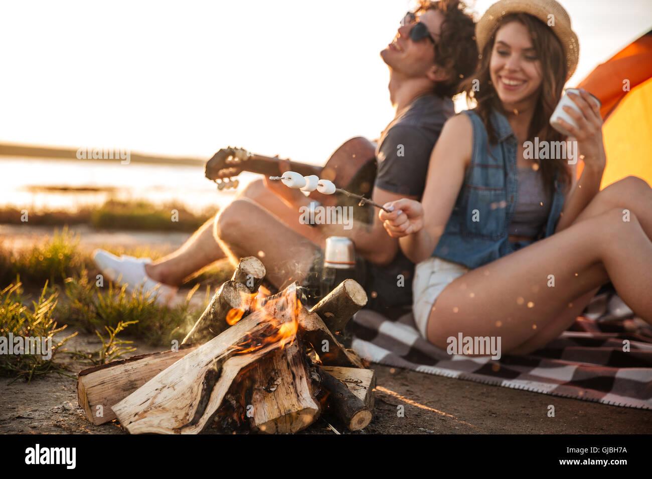 Alegre hermosa pareja joven tocando la guitarra y freír malvaviscos en la fogata Imagen De Stock