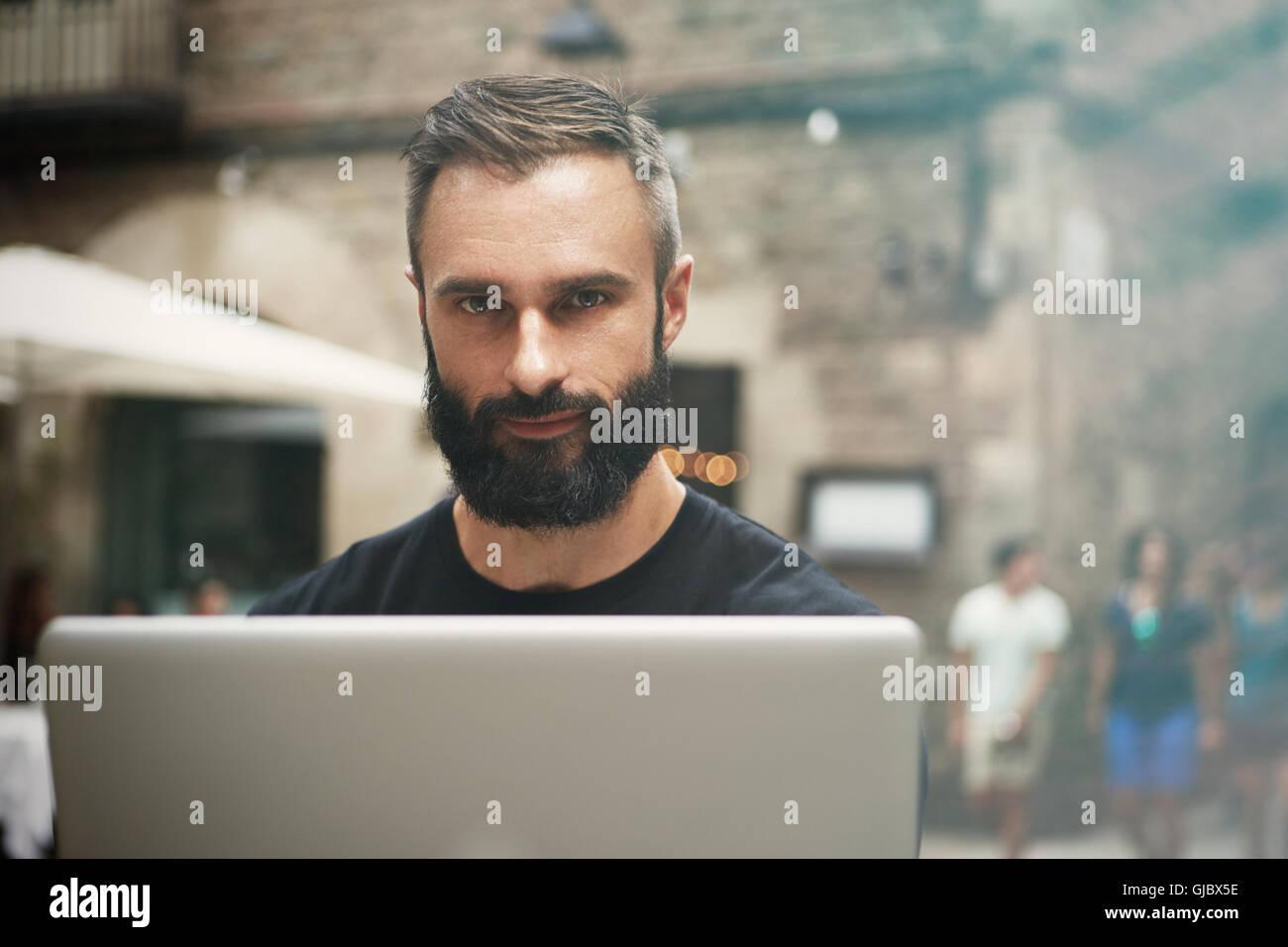 Closeup retrato guapo empresario barbudo vistiendo negro Tshirt Trabajo Urbano portátil Cafe.Joven Manager portátil de trabajo exterior.Coworking proceso Business Startup.fondo difuminado. Foto de stock