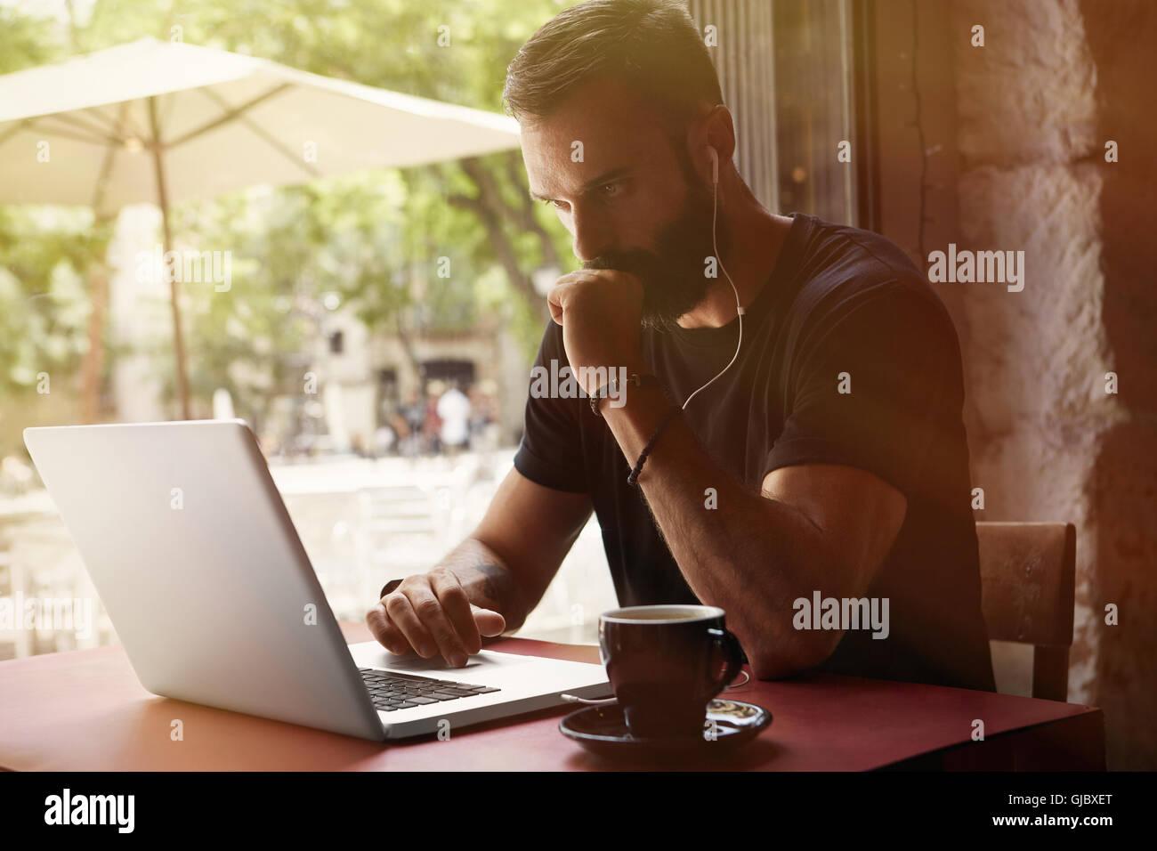 Empresario joven barbudo concentrada vistiendo negro Tshirt Trabajo Urbano portátil Cafe.hombre sentado Tabla Imagen De Stock