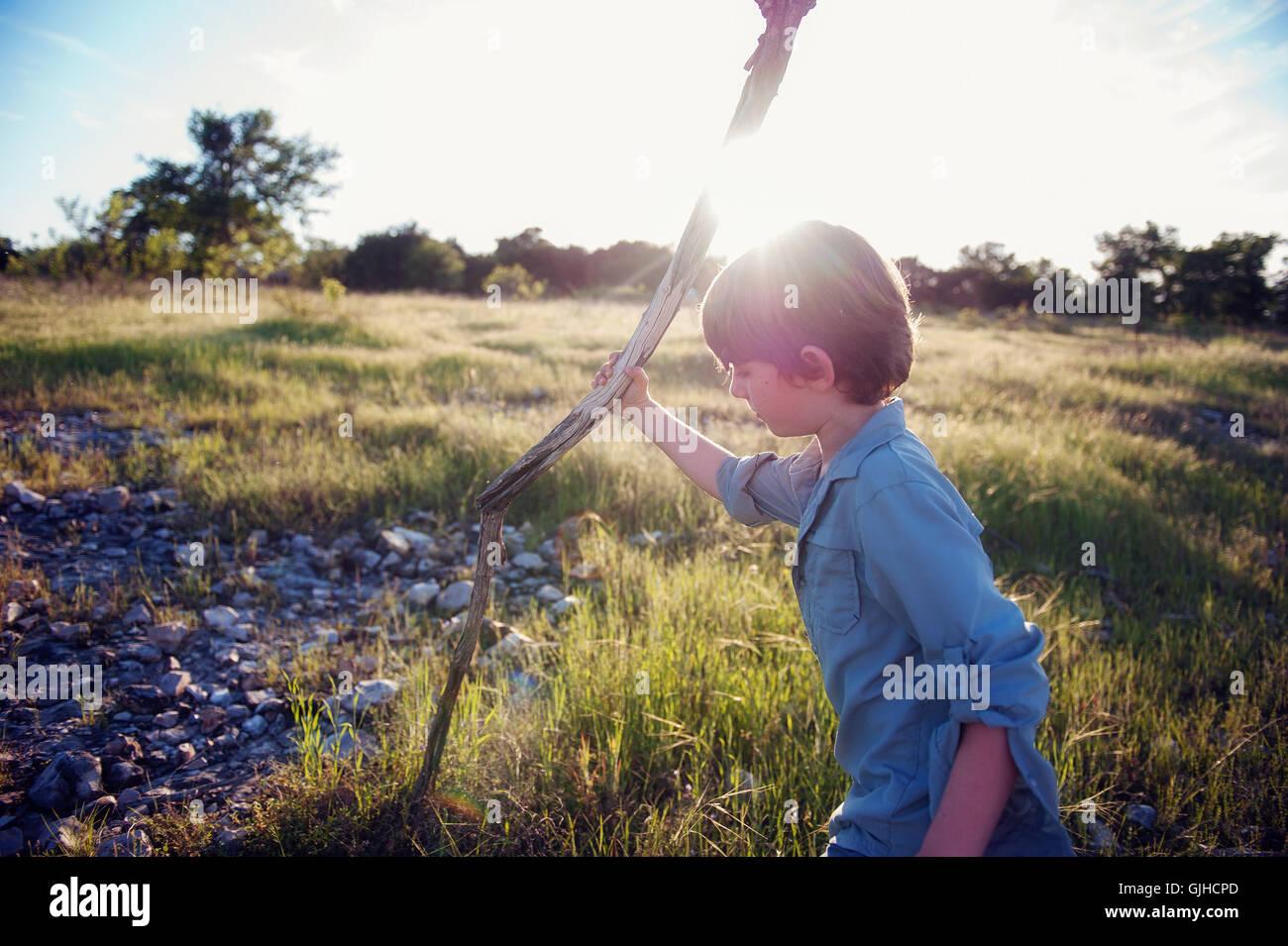 Niño sosteniendo un bastón de madera a pie Imagen De Stock