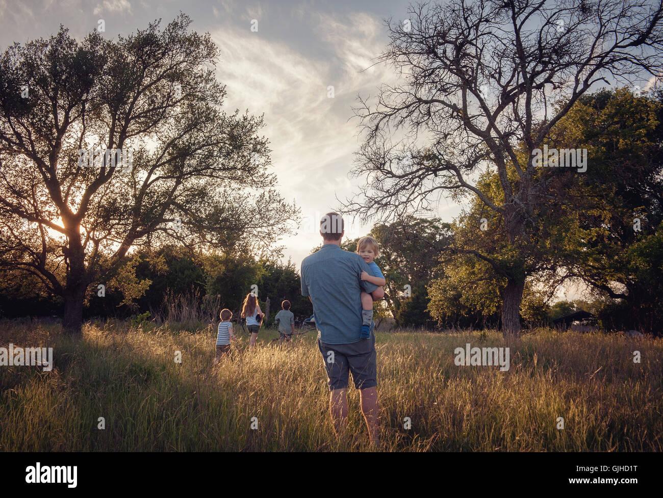 Padre y cuatro hijos andando en paisaje rural al atardecer, Texas, Estados Unidos, EE.UU. Imagen De Stock