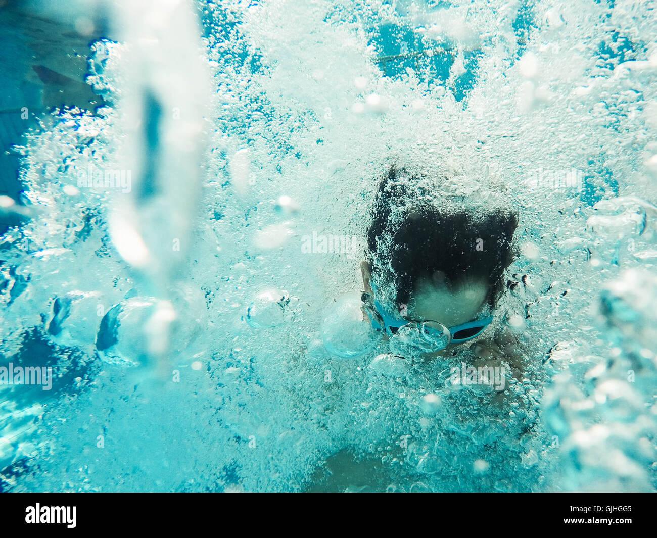 Vista submarina de boy saltando a una piscina Foto de stock