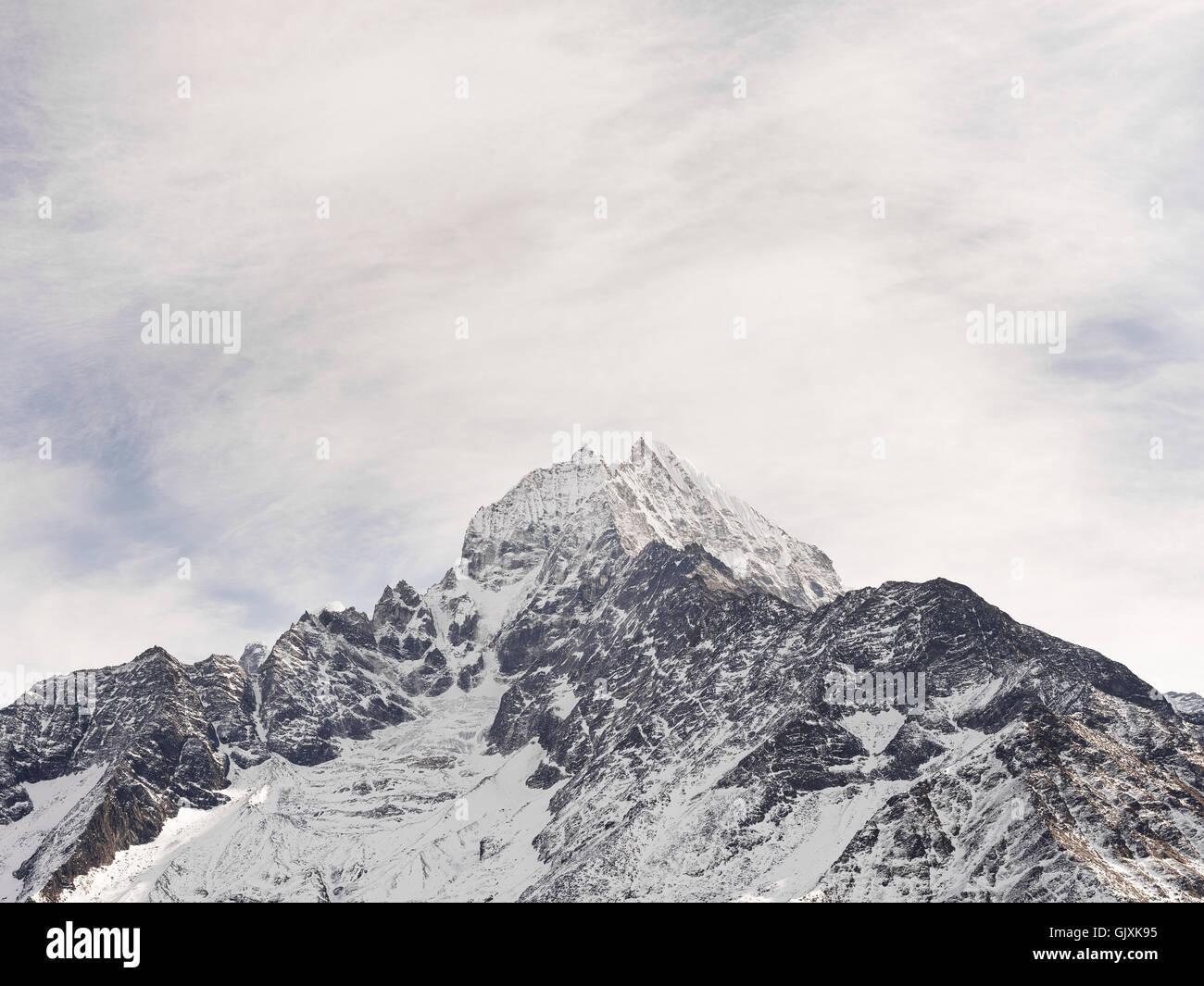 Pico cubierto de nieve de un dentado de las montañas del Himalaya de Nepal en el campamento base del Everest Imagen De Stock