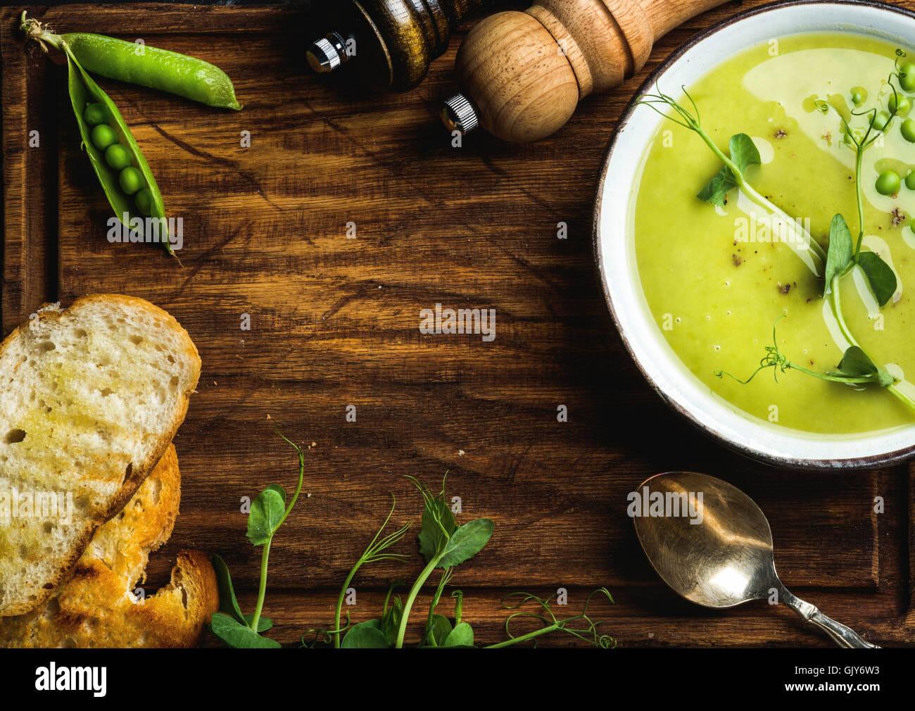 Pease casera dulce sopa crema en el tazón con pan blanco sobre fondo de madera rústica, vista superior, Imagen De Stock