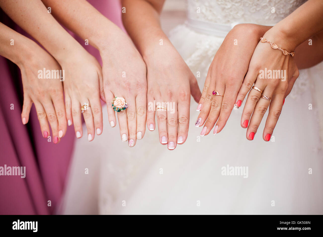 La novia y las damas de honor están mostrando sus manos con anillos ...