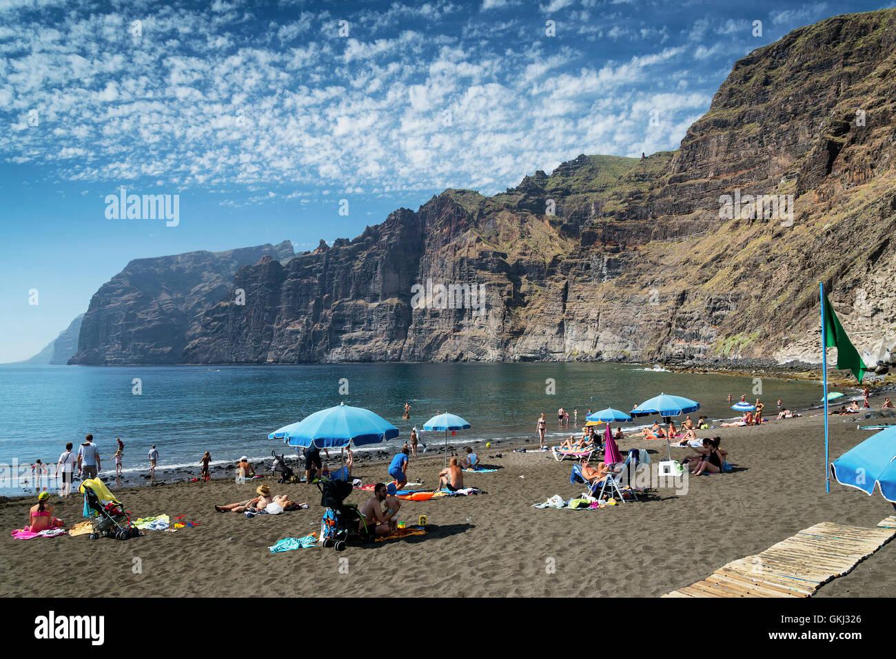 Acantilados de los gigantes a los turistas en la playa de arena negra volcánica hito natural en el sur de la Imagen De Stock
