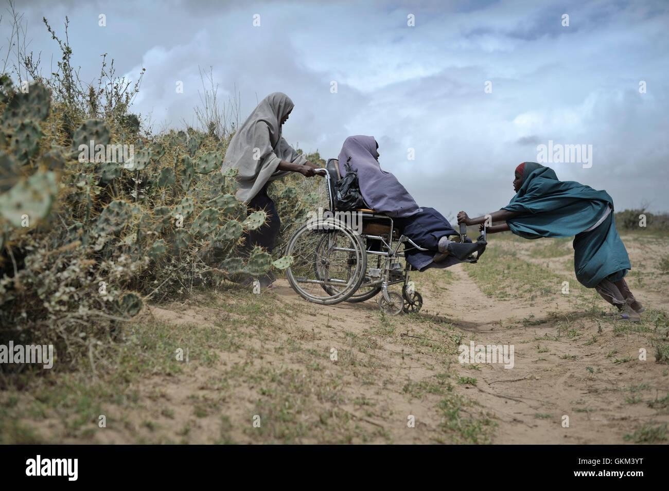 Dos mujeres ayudar a otro a través de un seto de cactii en un centro de distribución de alimentos en Afgoye, Imagen De Stock