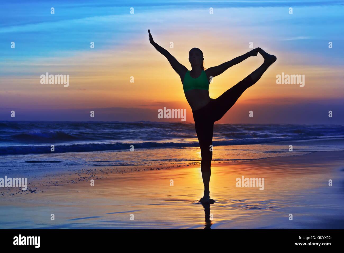 Silueta negra de mujer estiramientos en yoga retreat en Sunset, la playa de arena colorida cielo, Ocean Surf de fondo. Estilo de vida deportiva Foto de stock