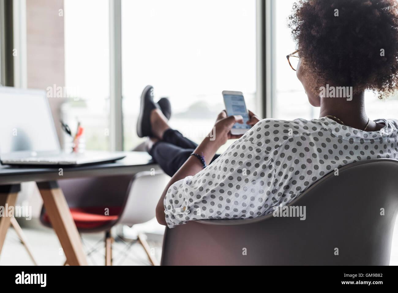 Vista posterior de la mujer la mensajería de texto Imagen De Stock