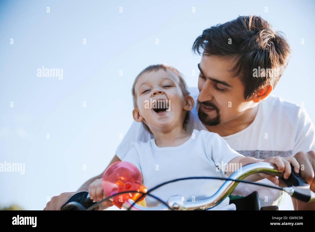 Laughing muchachito en excursión en bicicleta con su padre Imagen De Stock