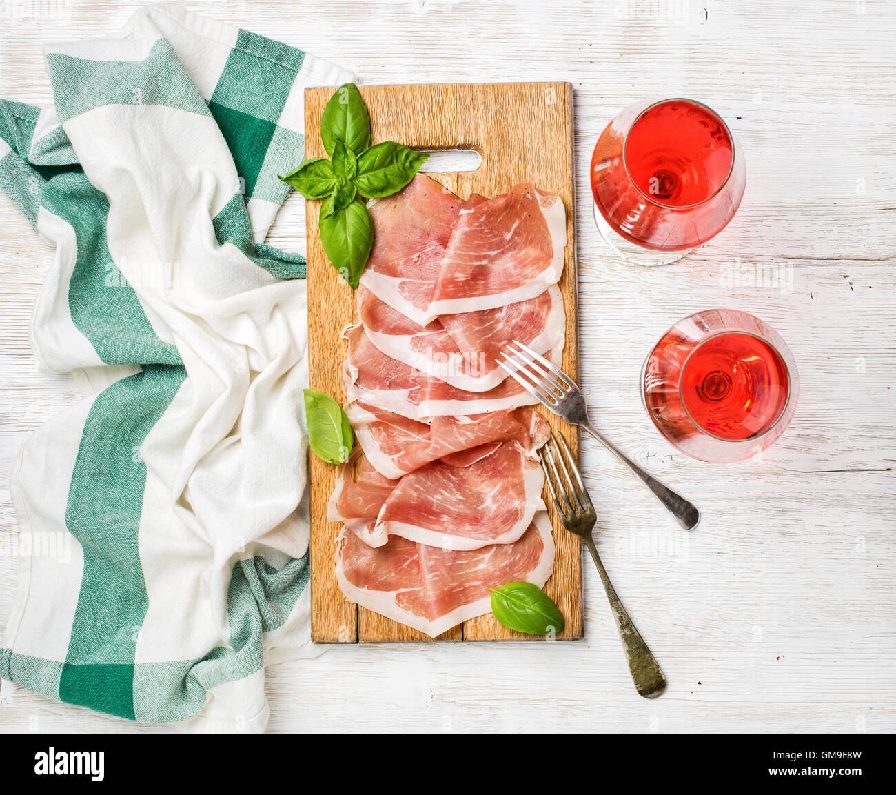 Lonchas de jamón prosciutto di Parma y Rose, copas de vino Imagen De Stock