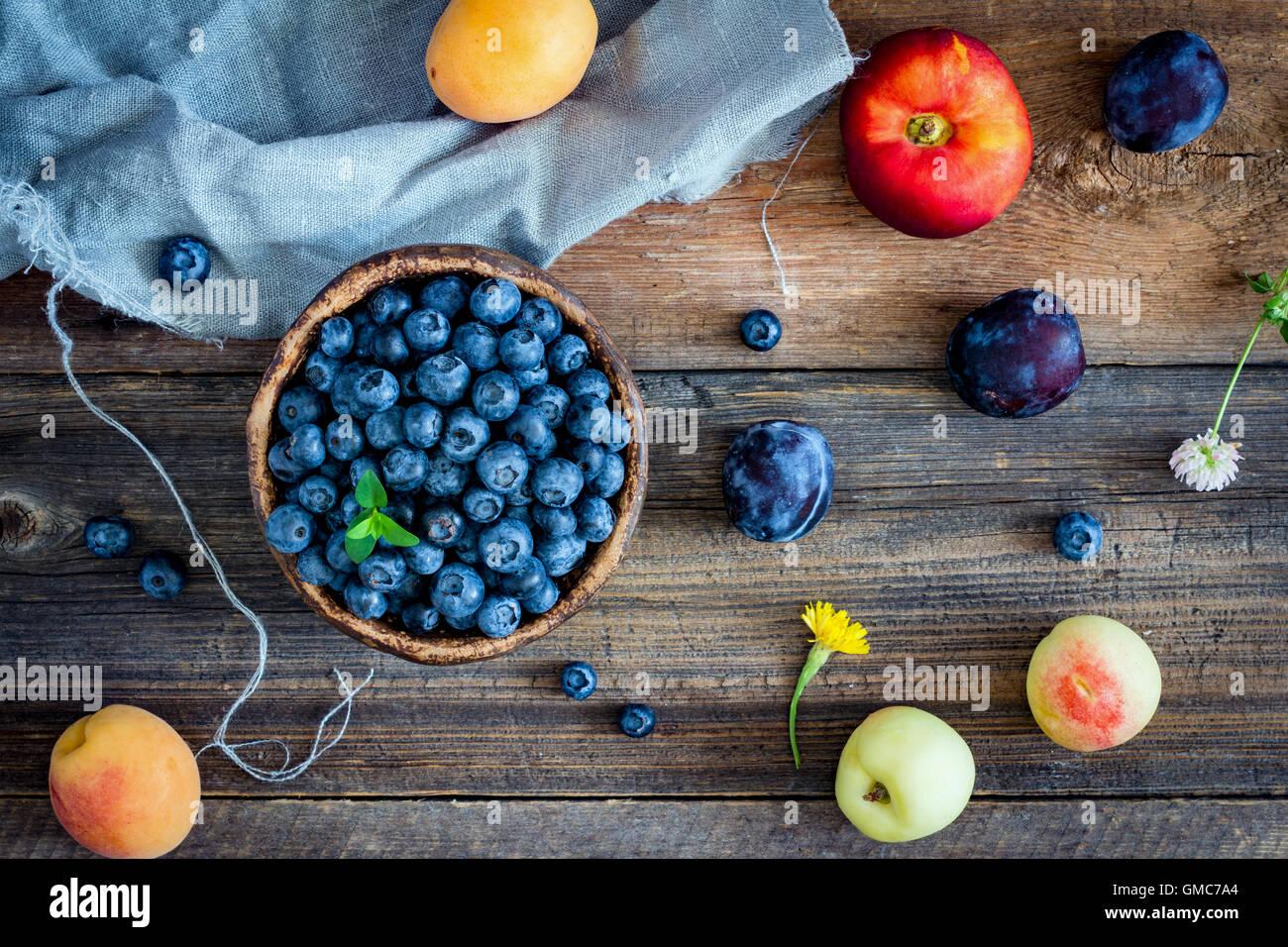 Frutas y bayas sobre fondo de madera. Coloridos frutos laicos plana Imagen De Stock