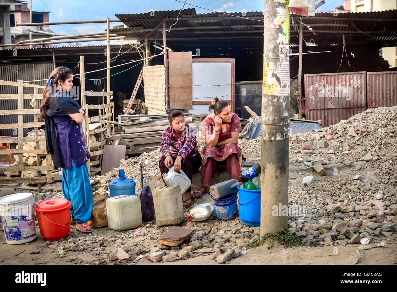 Las mujeres esperan el agua carretilla delante de refugios temporales durante la estación seca en Katmandú, Imagen De Stock