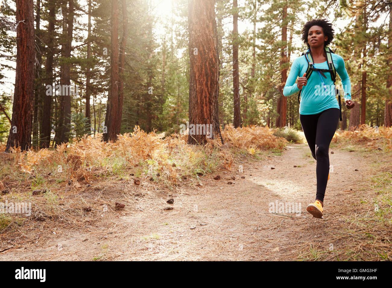 La etnia afroamericana mujer corriendo en un bosque Imagen De Stock