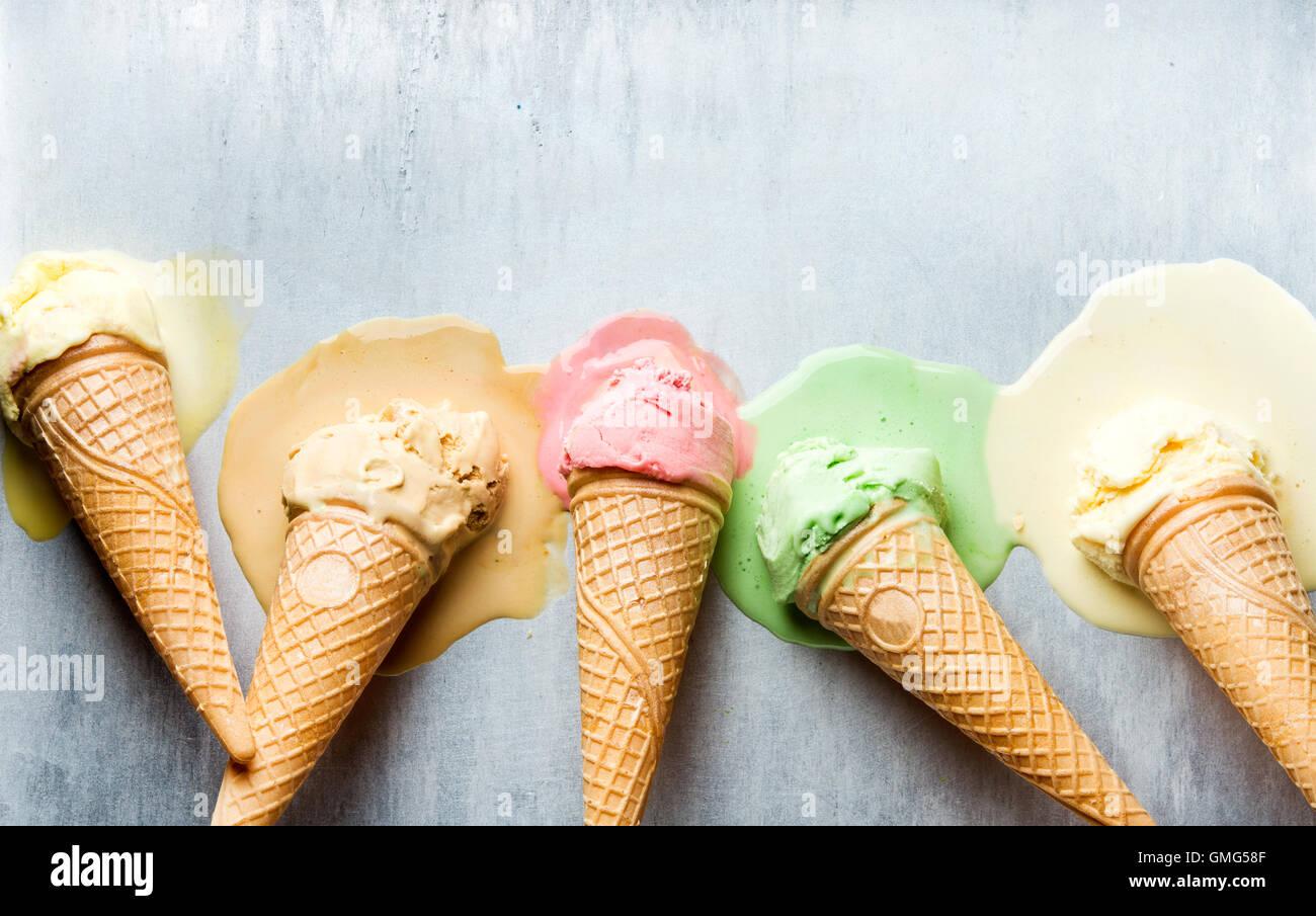Coloridos conos de helado de diferentes sabores. Bocas de fusión. Vista superior, fondo de metal de acero Imagen De Stock