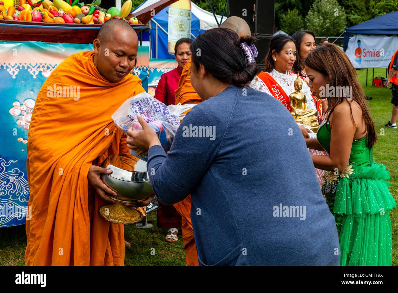 Los Tailandeses ofrecen comida a dos Monjes en el Brighton Festival Tailandés, Preston Park, Brighton, Sussex, Imagen De Stock