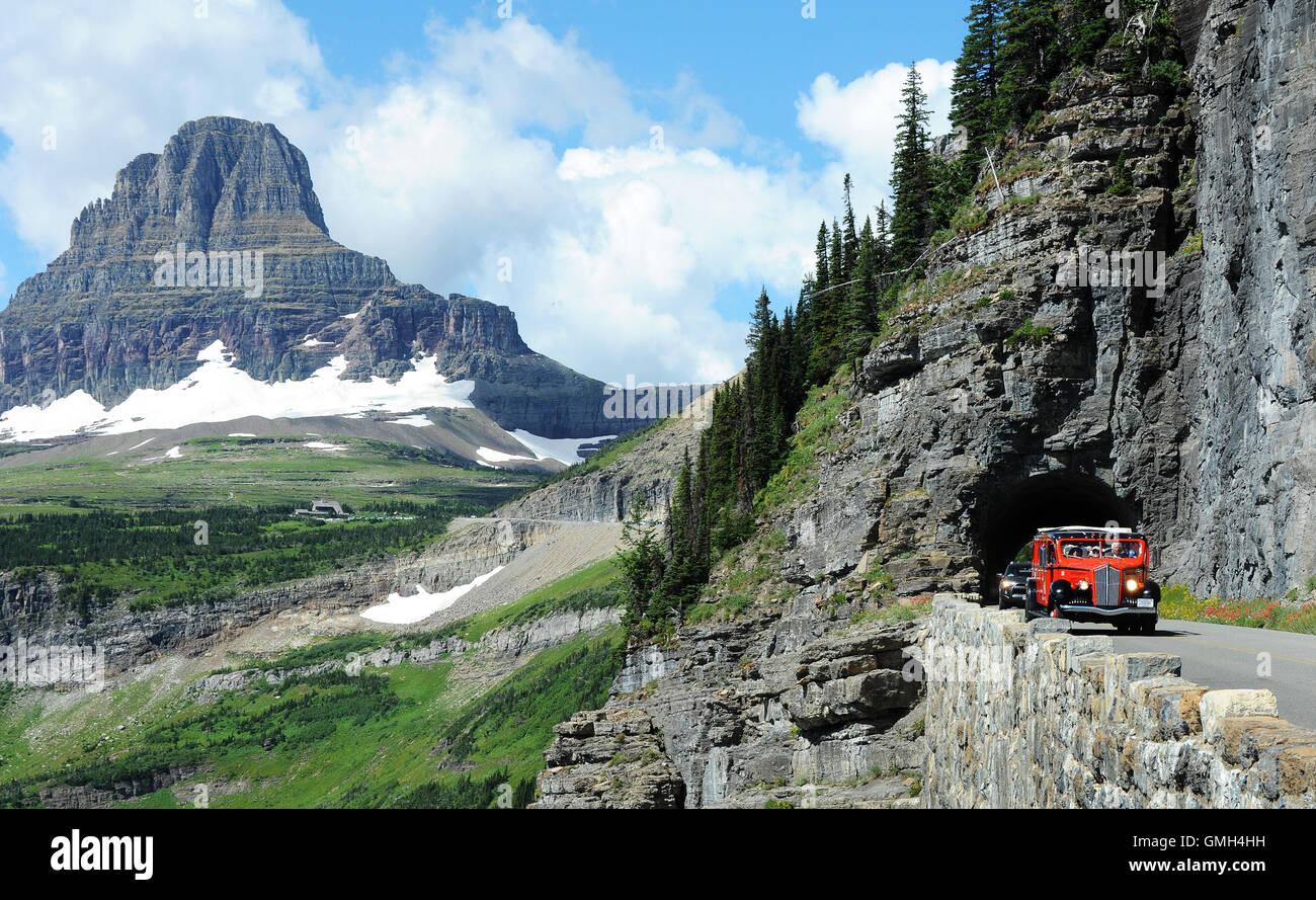 Agosto 12, 2016 - El Parque Nacional Glacier, Montana, Estados Unidos - 1930 era rojo tour bus pasa a través Imagen De Stock