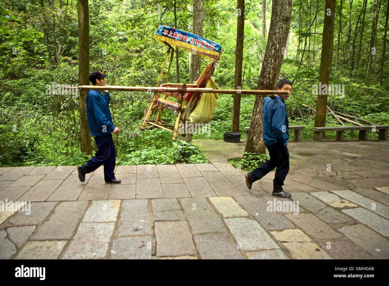 Dos hombres que ocupan una silla vacía para el transporte de personas en el Parque Forestal Nacional de Zhangjiajie, Foto de stock