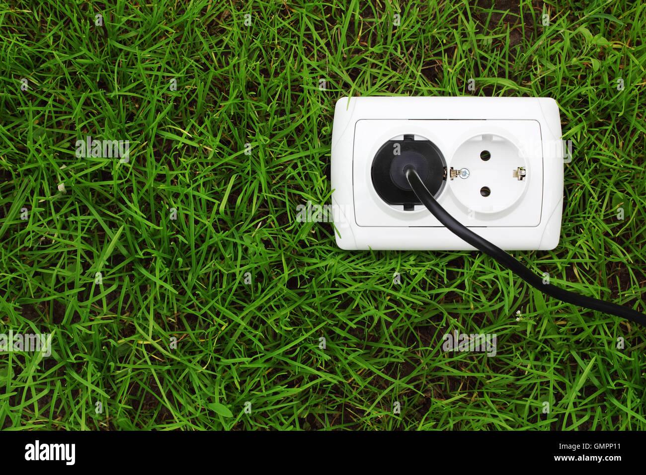 Receptáculo de alimentación eléctrica sobre un fondo de hierba verde Imagen De Stock