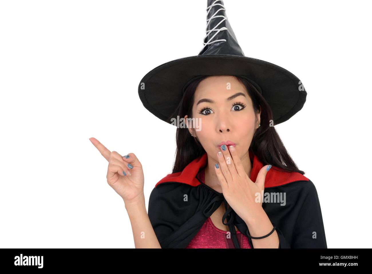 Chica guapa en traje de bruja que una mano apuntando hacia la