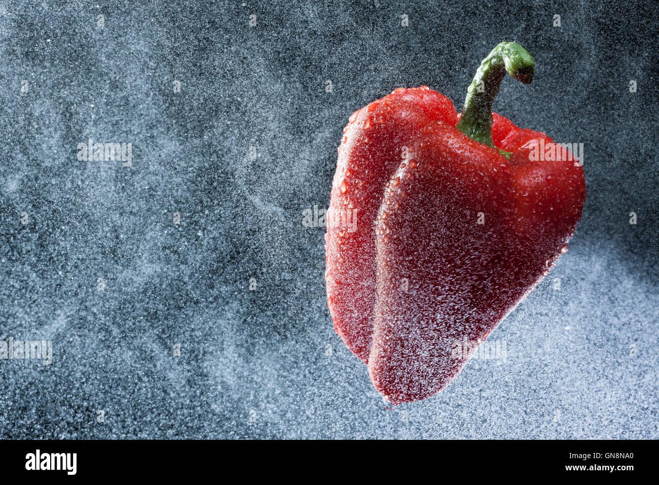 Pimiento rojo en un spray contra un fondo negro. Una serie de frutas y verduras en movimiento. Foto de stock