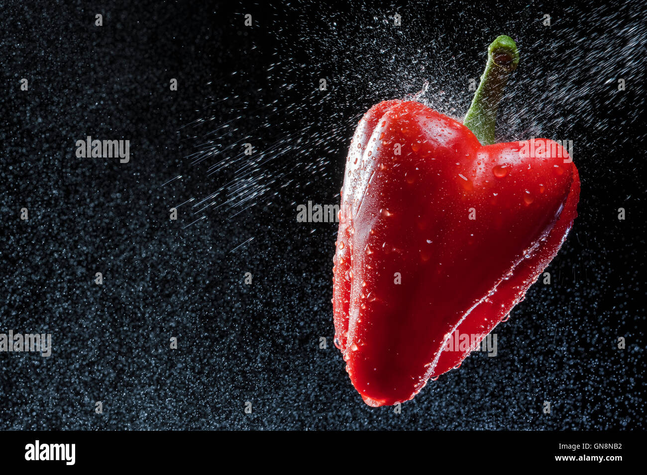 Pimiento rojo en un spray contra un fondo negro. Una serie de frutas y verduras en movimiento. Imagen De Stock