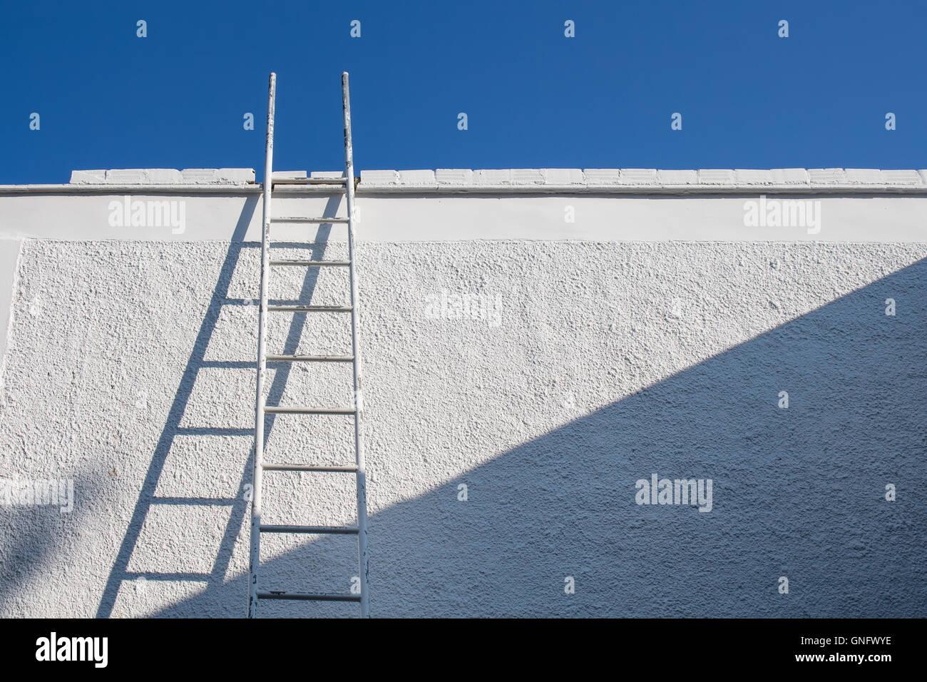 Escalera de color blanco al lado de una pared blanca. El azul claro del cielo sin nubes. Imagen De Stock
